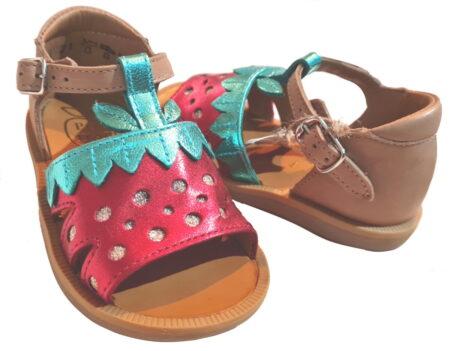 Un cuir lisse camel avec une fraise en cuir métal vert et rouge sur l'avant du pied pour la Poppy Berry fermée par 1 bride à boucle. un nu-pied bébé fille signé Pom d'Api
