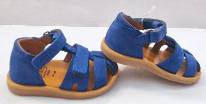 Un nu-pied à bout protégé en cuir nubuck cobalt pour premiers pas garçon. Ce modèle est fermé par 1 velcro et doté d'une bride velcro sur le pied. chaussure enfant Poppy Boy strap de Pom d'Api