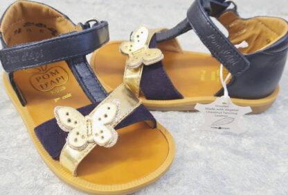 Une mixité de cuir lisse velours marine avec lanière métal or pour le nu-pied premiers pas Poppy cross. Cette sandale enfant Pom d'Api est fermé par 1 bride à velcro