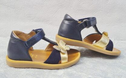 Poppy Cross de Pom d'Api, une sandale premiers pas en cuir marine dotée de 2 lanières cuir velours marine et métal or dotées d'un joli papillon or et glitter argent. Un nu-pied fermé par 1 bride à velcro.