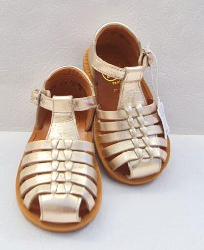 Poppy Pitti, une sandale premiers pas en cuir laminé platine dotée de multiples lanières, d'un contrefort fermé par 1 bride à boucle. une chaussure enfant Pom d'Api