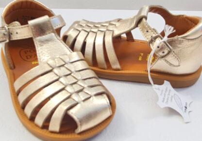 Un style salomé avec de multiples lanières en cuir laminé platine pour le nu-pied fermé enfant Poppy Pitti de Pom d'Api. Cette sandale est dotée d'un contrefort et fermée par 1 bride à boucle