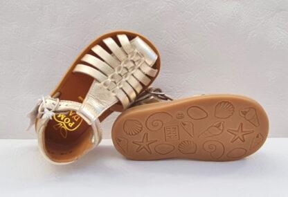 une sandale Pom d'Api pour premiers pas Poppy Pitti en cuir platine. Ce nu-pied est doté d'un contrefort avec col matelassé et se ferme par 1 bride à boucle