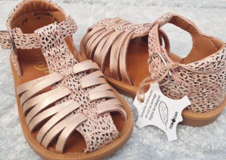 un nu-pied fermé pour premiers pas en cuir cuivré imprimé et lanières entrecroisées cuivrées. Ce modèle signé Pom d'Api est fermé par 1 bride à boucle