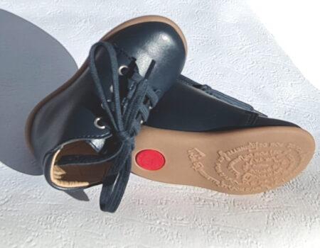 Chaussure pour premiers pas en cuir de pomme Stand Up Bottine de Pom d'Api. ce modèle en cuir marine est fermé par 1 lacet