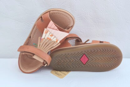 Tity Falls est un nu-pied avec contrefort en cuir lisse camel, doté de franges sur le pied en cuir irisé taupe, métalisé platine imprimée pailleté rose lisse rose, modèle Shoo Pom fermé par 1 bride à velcro