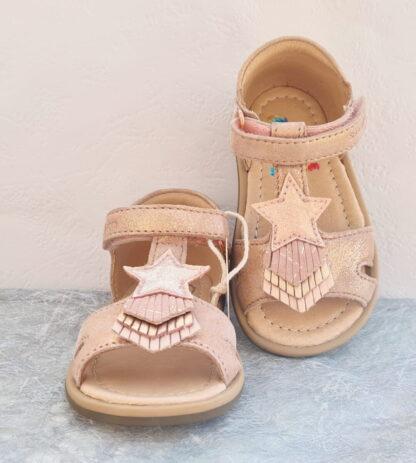 Tity Kid, un nu-pied premiers pas en cuir velours nude irisé doté d'une bride style salomé joliment décorée d'une étoile et de 3 petites franges. Modèle Shoo Pom fermé par 1 bride à velcro