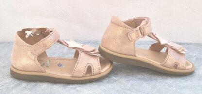 Un nu-pied pour premiers pas Shoo Pom. Modèle avec contrefort fermé par 1 velcro. Une sandale en cuir velours nude irisé et doté d'une bride salomé décorée d'une étoile et de 3 petites franges